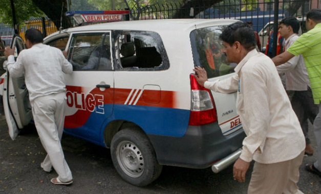 Police personnels push damaged police patrolling van, after a confrontation between Delhi police and stunt bikers at Windsor place in New Delhi on Sunday - PTI